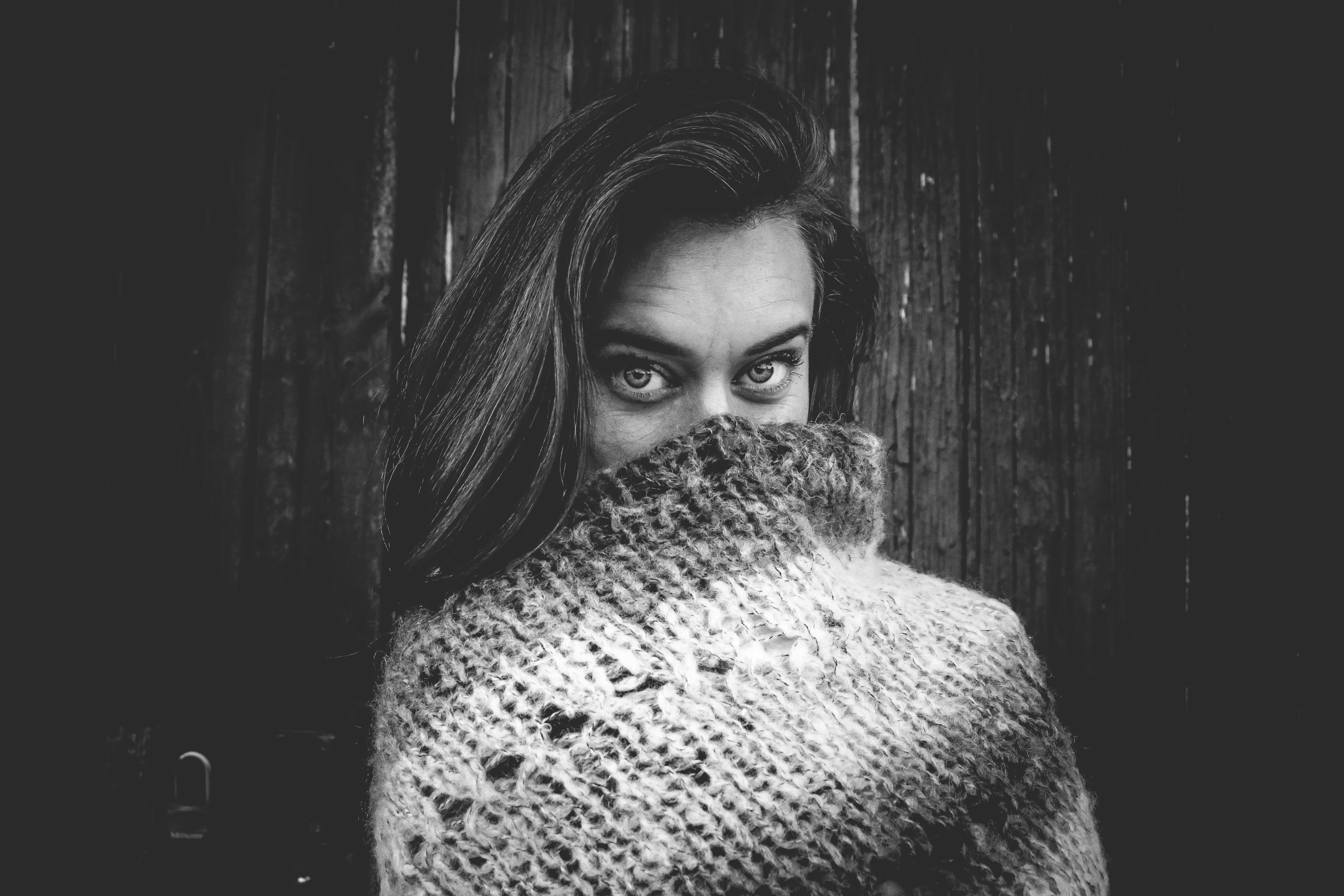 Grayscale Photo of Woman Covering Mouth With Knitted Textile