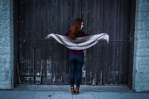 Woman Holding Gray Shawl While Spreading Her Arms Infront of Brown Wooden Door