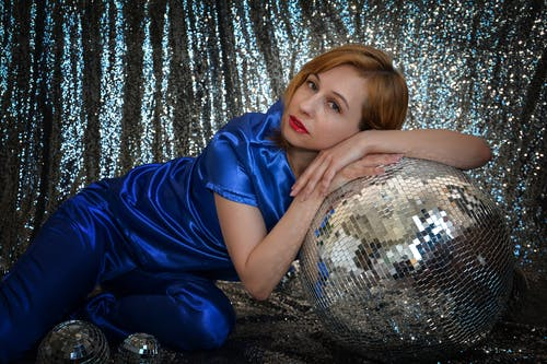 Stylish female in blue outfit looking at camera while sitting on floor with decorative shining disco balls on silver background