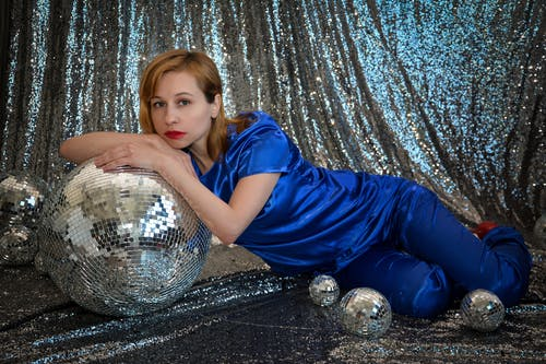 Stylish female model looking at camera while lying on floor with various decorative disco balls on silver background in studio