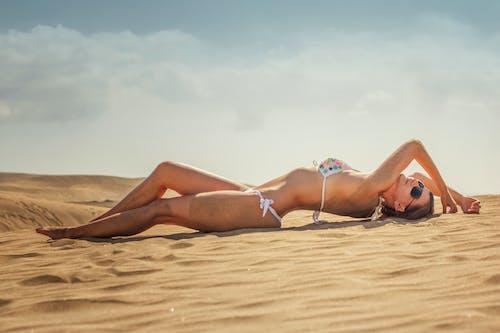 Woman in Blue Bikini Lying on Sand