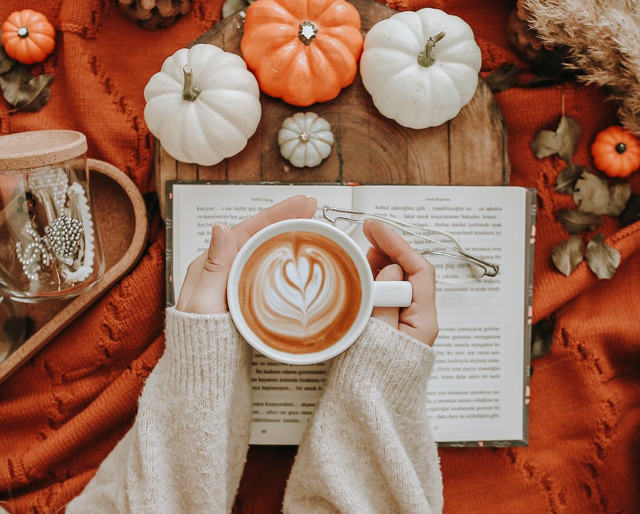 Anonymous woman with coffee near pumpkins