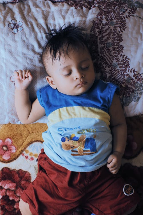 From above of calm ethnic little boy in casual clothes lying on comfortable bed and sleeping at home in daytime