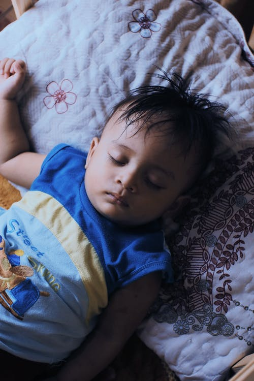From above of tranquil little ethnic boy with dark hair in casual clothes lying on soft pillow on bed and sleeping in daytime