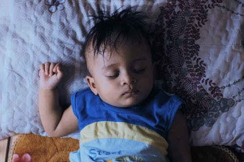 Little ethnic kid sleeping on comfortable bed at home