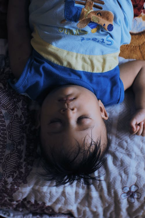 From above of calm little ethnic kid in pajama lying on comfortable blanket on bed in bedroom at home