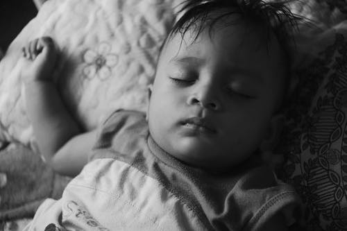 Black and white of calm ethnic kid in pajama lying with closed eyes on comfortable bed in bedroom at home in daytime