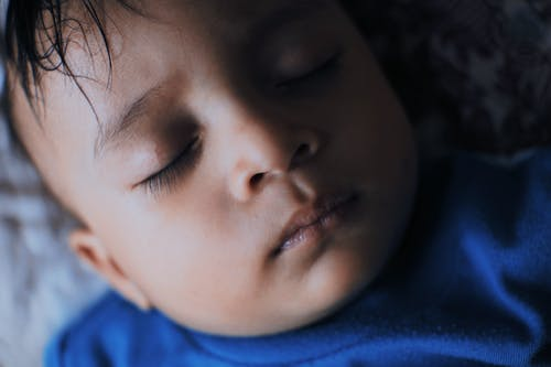 Tranquil ethnic boy sleeping on bed