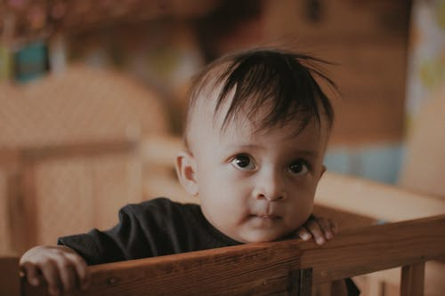 Adorable little ethnic baby with brown eyes and messy hair standing in crib and looking away with curiosity