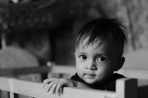 Grayscale Photo of a Child Looking at Camera