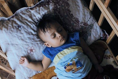 A Cute Boy Sleeping on a Wooden Crib