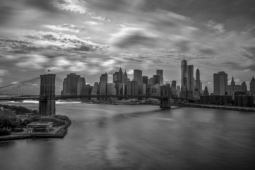 Grayscale Photography of City Buildings and Bridge