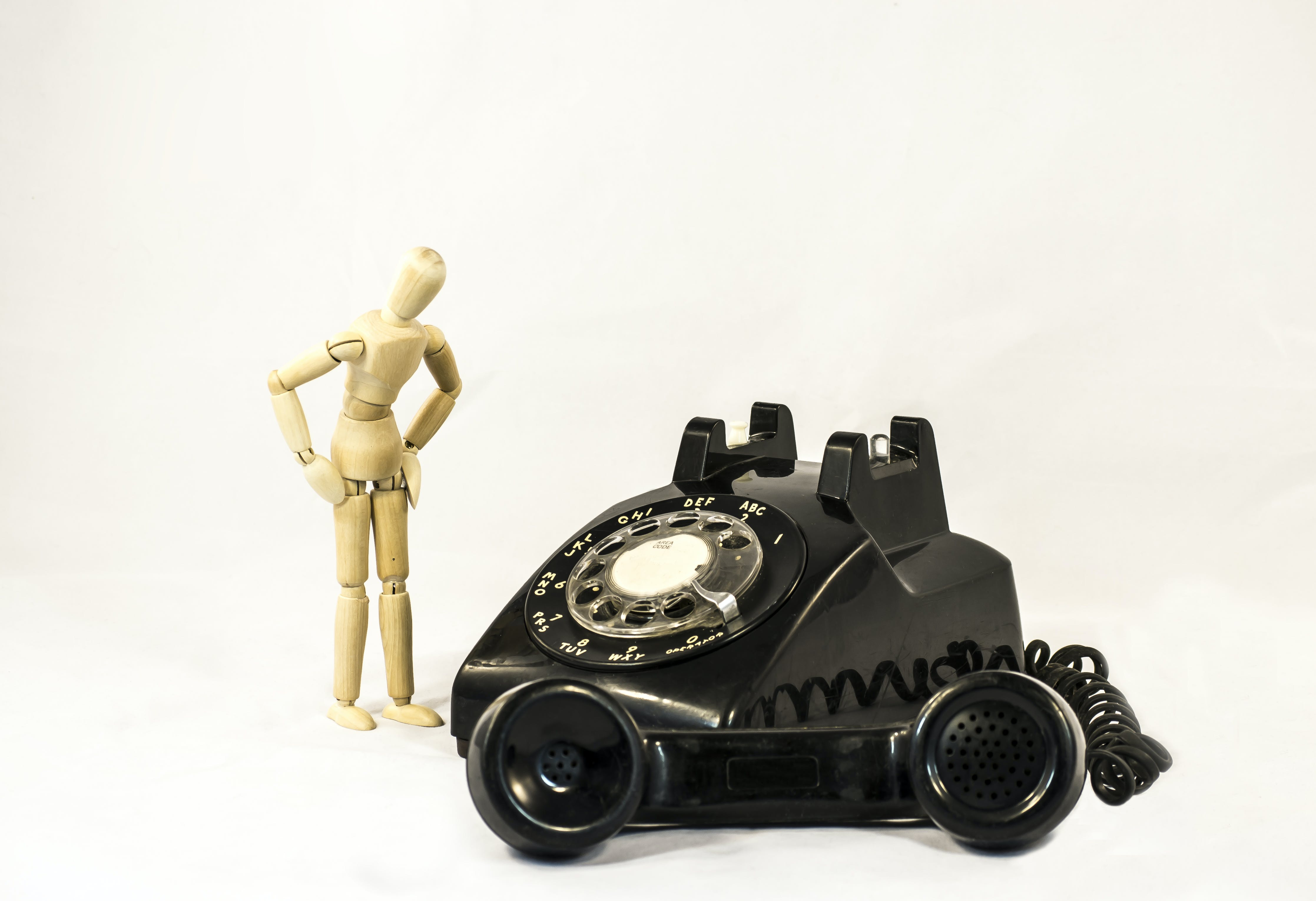 Black Rotary Telephone Beside Beige Manekin