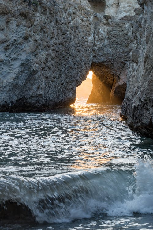 Sun Rays Coming Through Gray Rock Formation in the Sea