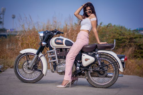 Woman in White Shirt and White Shorts Riding on White Motorcycle