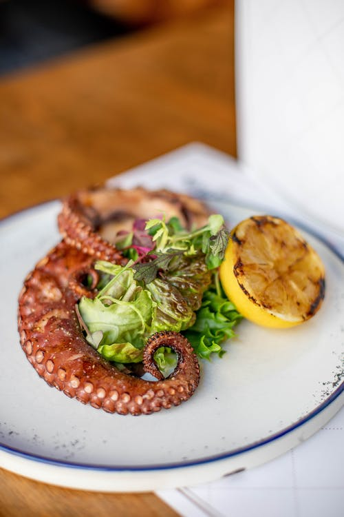 High angle of savory fried octopus tentacles served with lettuce leaves and lemon on plate