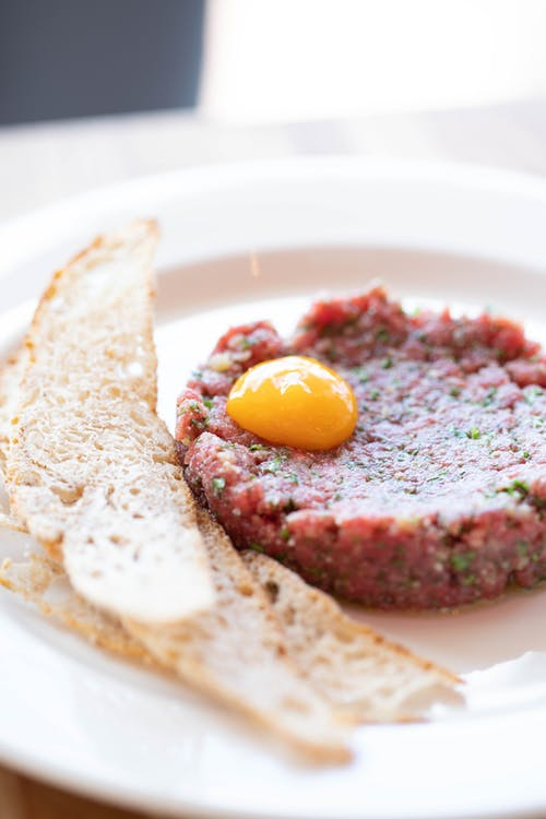 Savory beef tartare dish with raw egg yolk served on plate near crunchy croutons during lunch
