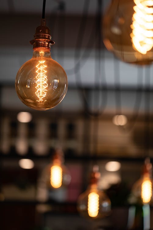 Soft focus of retro electric light bulb hanging on ceiling and illuminating cafeteria