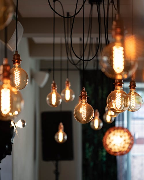 Bunch of vintage electric light bulbs hanging on wires and glowing inside cozy cafe