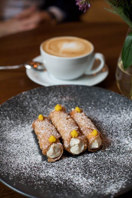 Cannoli dessert near coffee in cafeteria