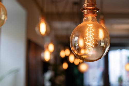 Reflective vintage light bulb shining brightly on blurred background of pub in evening