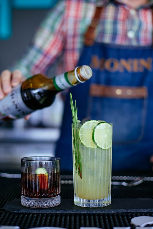 Unrecognizable bartender pouring gin from bottle into glass with slices of fresh lime and rosemary served near glass filled with tasty negroni cocktail in daylight