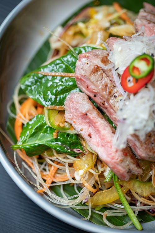 Closeup of delicious funchose salad with meat and sauce in bowl on table