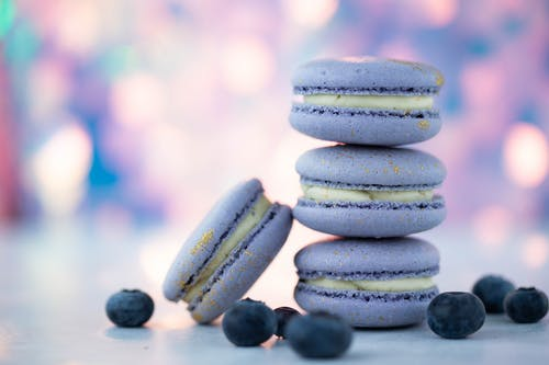 Gentle purple macaroons with white delicate cream near fresh ripe blueberries on blurred background