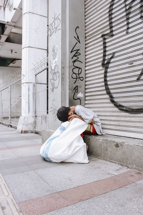 Man in White Robe Sitting on Sidewalk