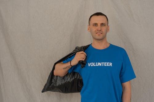Man in Blue Crew Neck T-shirt Holding Black Plastic Bag
