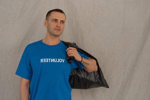 A Male Volunteer Holding a Garbage Bag