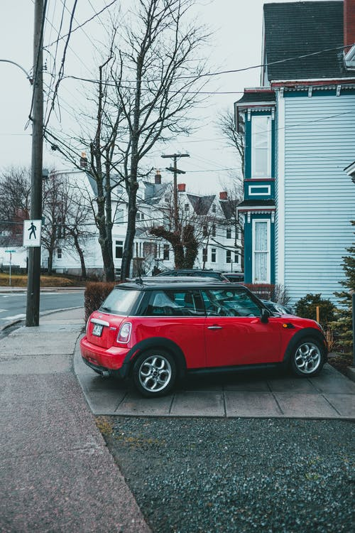 Red car parked near residential building in daytime