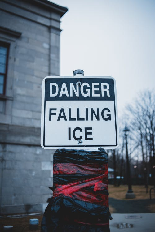 Danger warning sigh with inscription near building in winter day