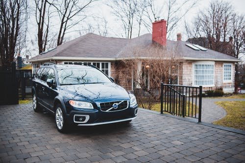 Exterior of new dark blue car placed near brick cottage surrounded by trees in cloudy day