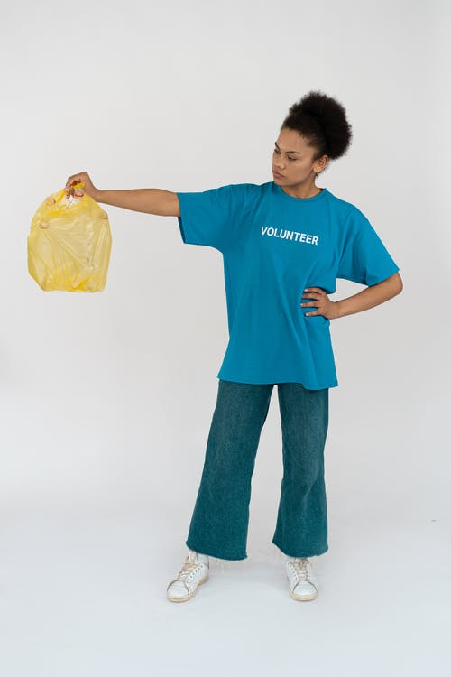 Woman in Blue Crew Neck T-shirt and Blue Denim Jeans Holding Yellow Plastic Bag