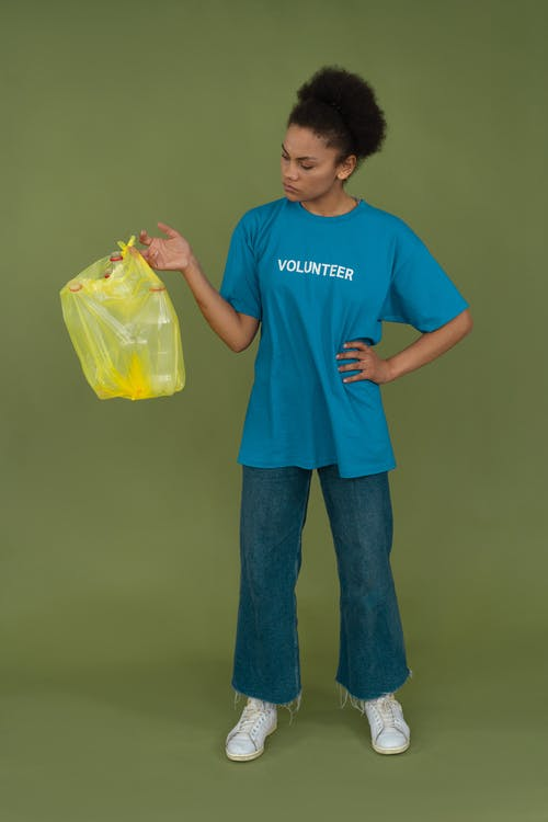 Woman in Blue Crew Neck T-shirt Holding Yellow Plastic Bag