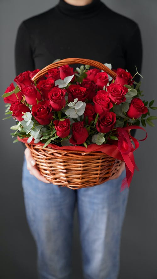 Crop unrecognizable female with wicker basket of blossoming red flowers with gentle buds and ribbon on gray background