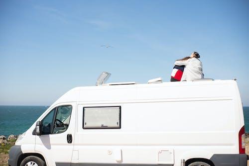 Man in White Shirt Sitting on White Van