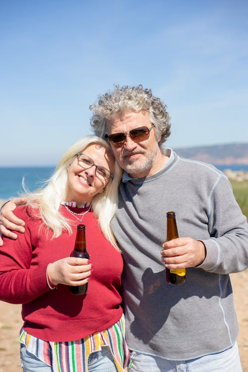 Photo of a Romantic Elderly Couple Holding Beers