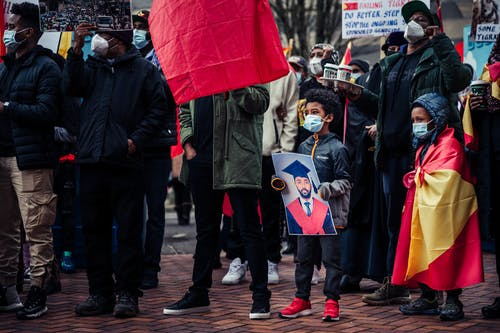 People in Black Coat Holding Red Umbrella