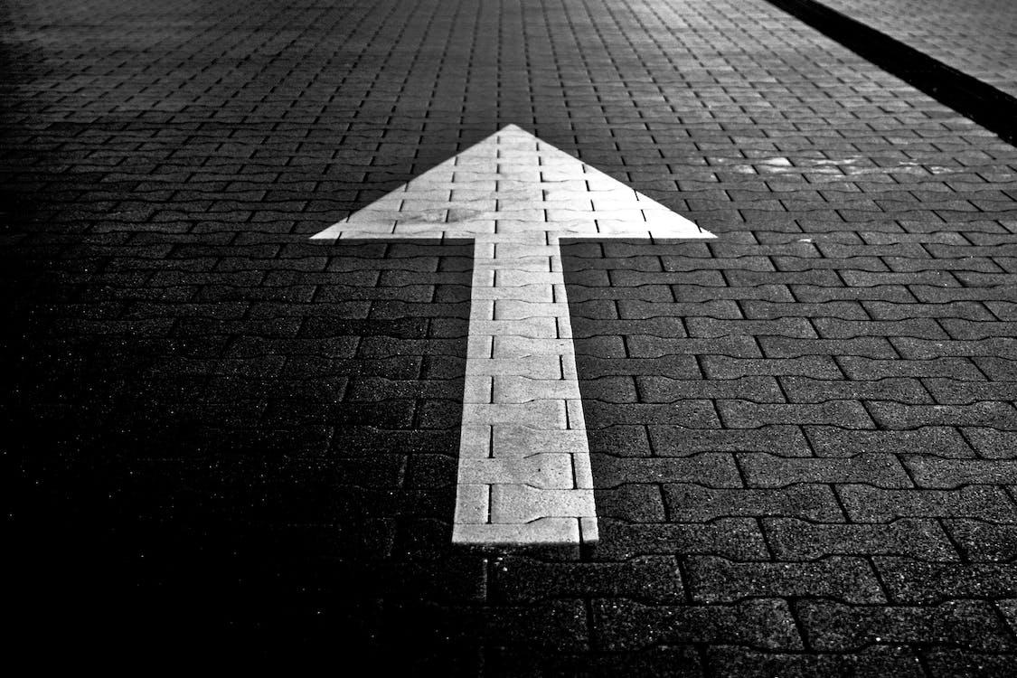 White Arrow Direction on Black Pavemet