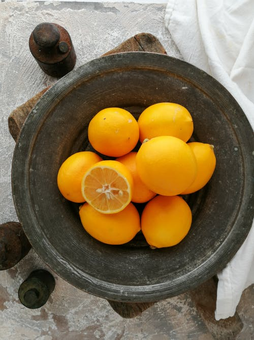 Yellow Citrus Fruits in Black Round Container