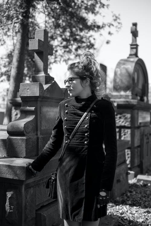 Woman in Black Jacket Standing Near Concrete Fence