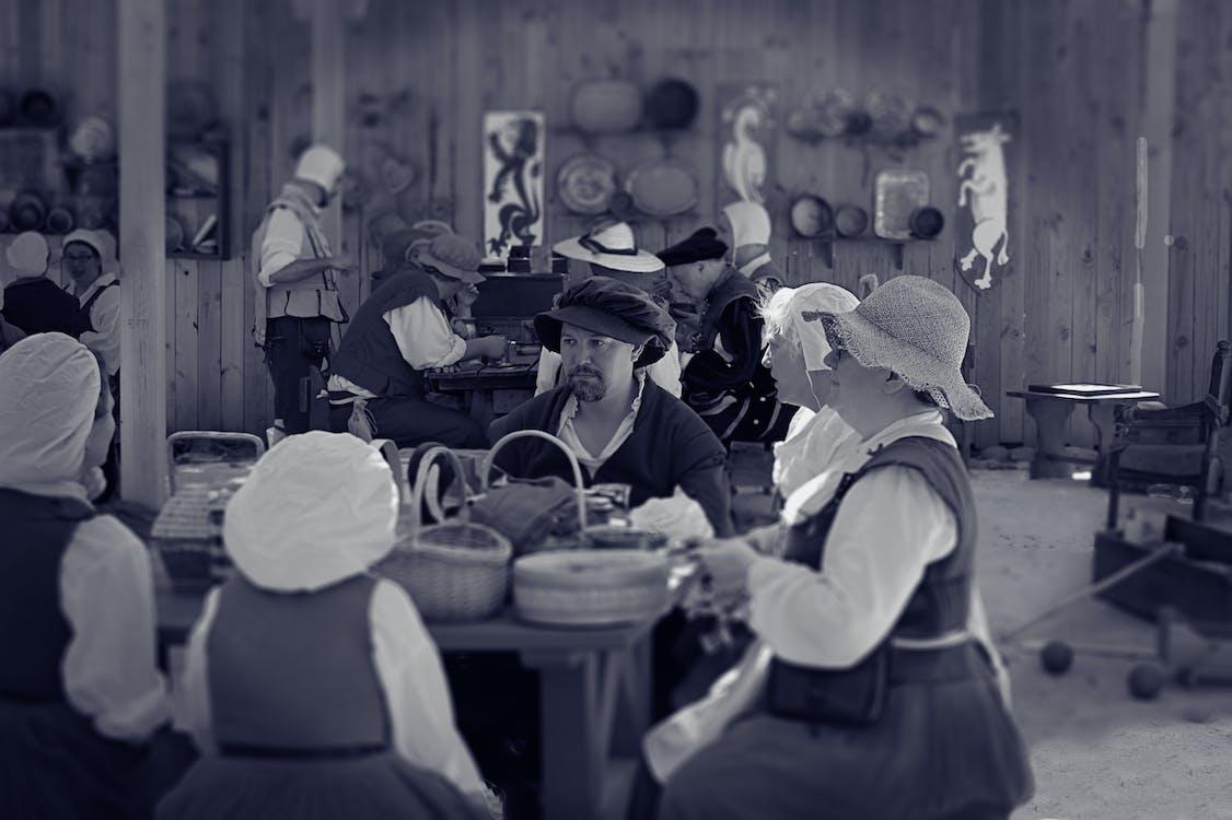 Man Sitting Between Female Near Table