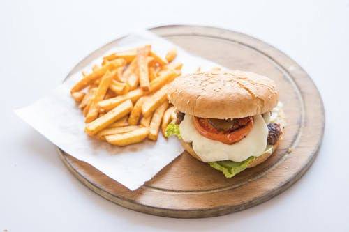 Burger and Fries on Brown Wooden Round Plate