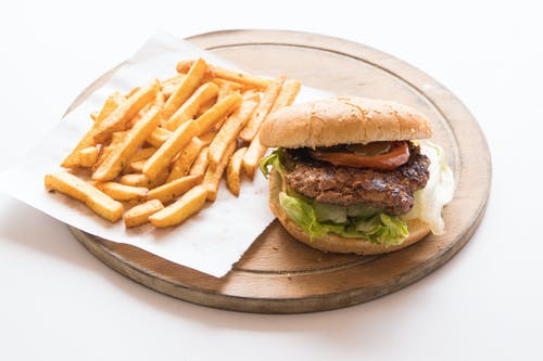 Burger and Fries on Brown Wooden Plate