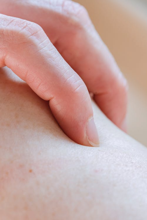 Closeup of crop anonymous person touching delicate skin of leg with hand while standing in light room on blurred background