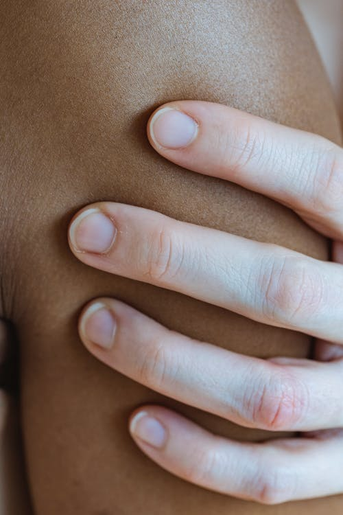 Closeup of crop faceless person touching arm of anonymous African American person with smooth skin in light room at home