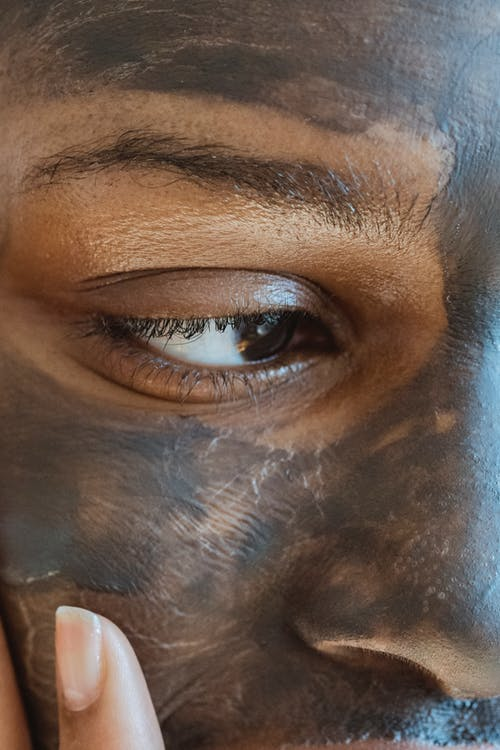 Black woman applying cosmetic mask on face
