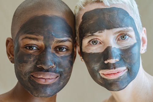 Crop positive diverse female friends with cosmetic masks on face looking at camera during spa procedures